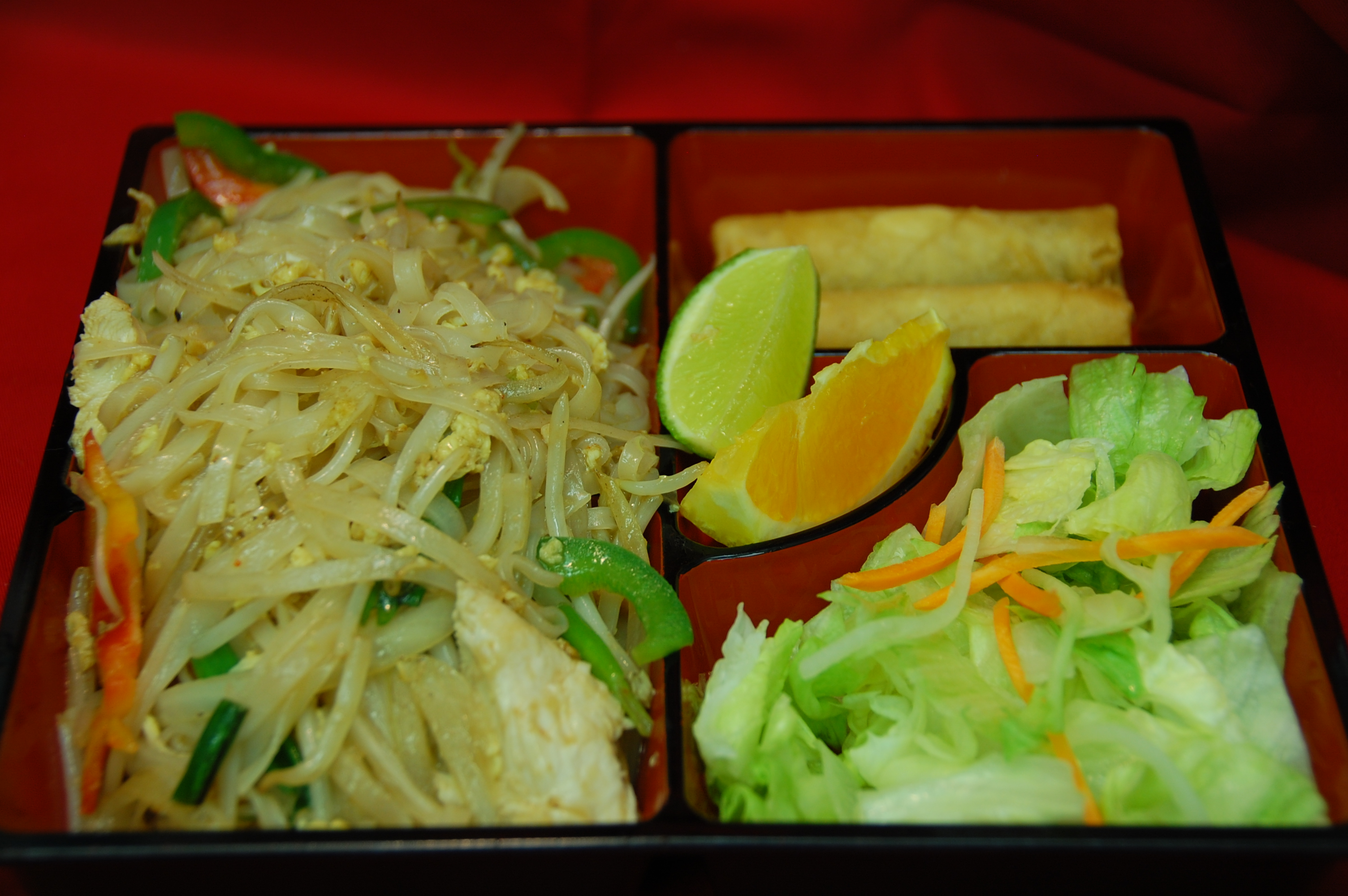 bento box filled with rice, egg rolls, salad and pad thai noodles