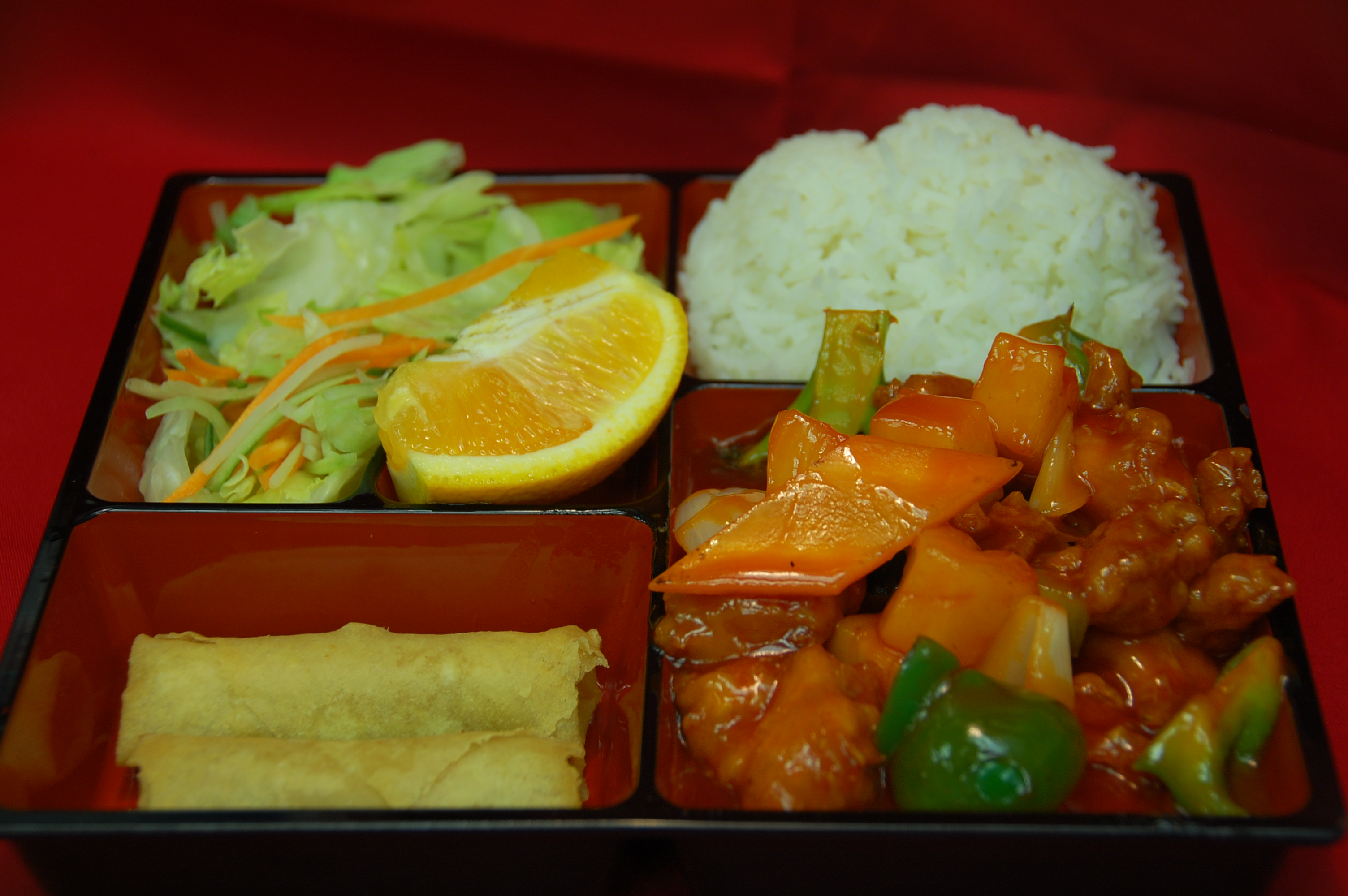 bento box filled with rice, egg rolls, salad and chicken sweet & sour with vegetables