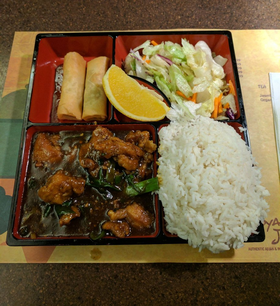 bento box filled with rice, egg rolls, salad and general tao chicken