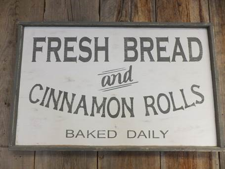 sign that says fresh bread and cinnamon rolls baked daily