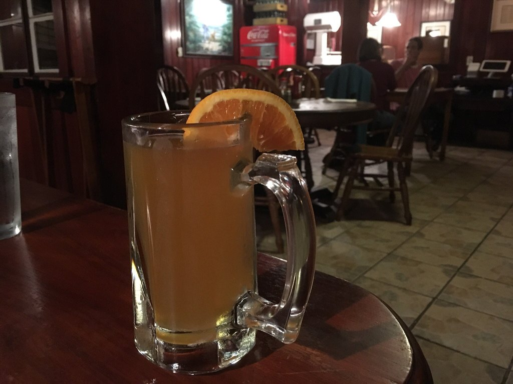 beer mug displayed on a table with an orange slice on the rim