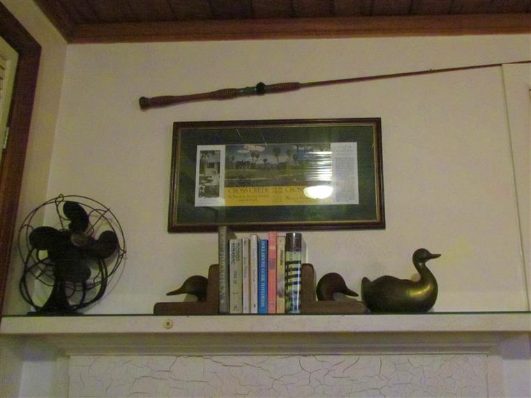 interior of cross creek cabin showcasing the fireplace mantel with books, fishing pole and a fan