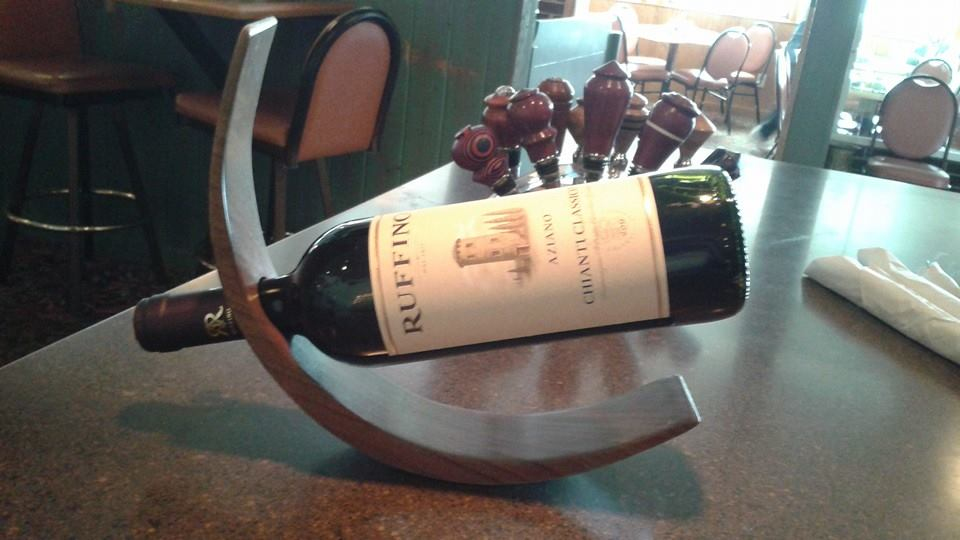 Curved wine bottle holder carrying a bottle of wine labeled Ruffino