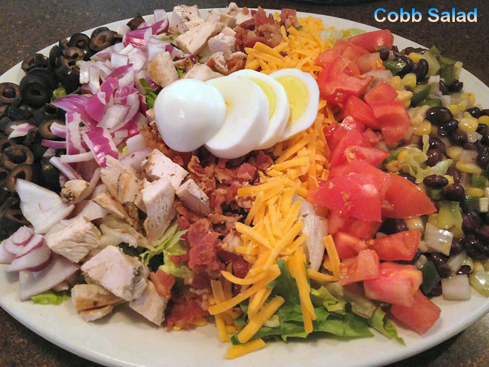 Chopped Coob salad layered with back olives, chopped red onions, diced chicken, bacon, yellow cheese, diced tomatoes, corn and a sliced boiled egg on top