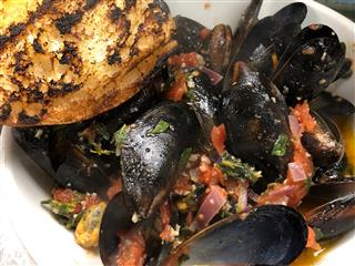Mussels with chopped onion an tomatoes in sauce with toasted bread