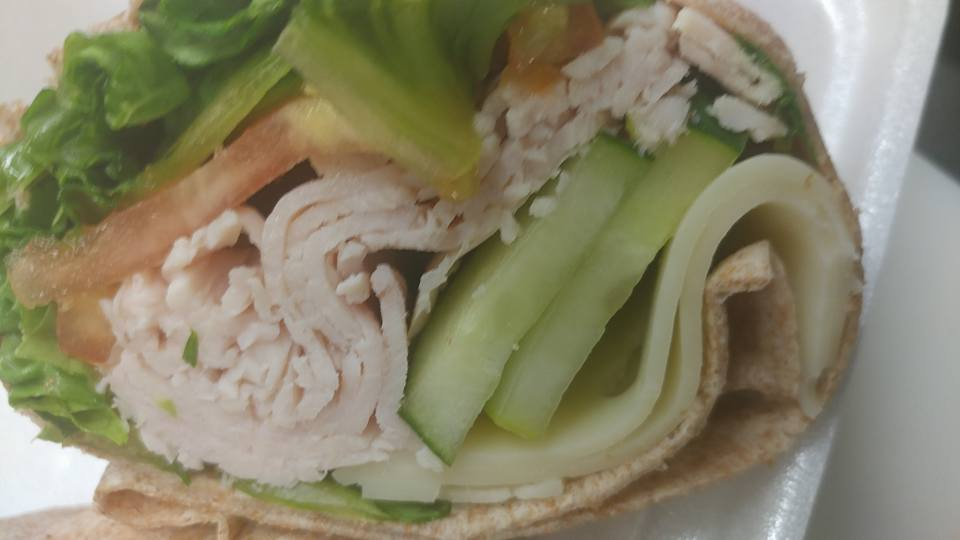 Turkey wrap topped with cucumbers, lettuce, cheese and tomato