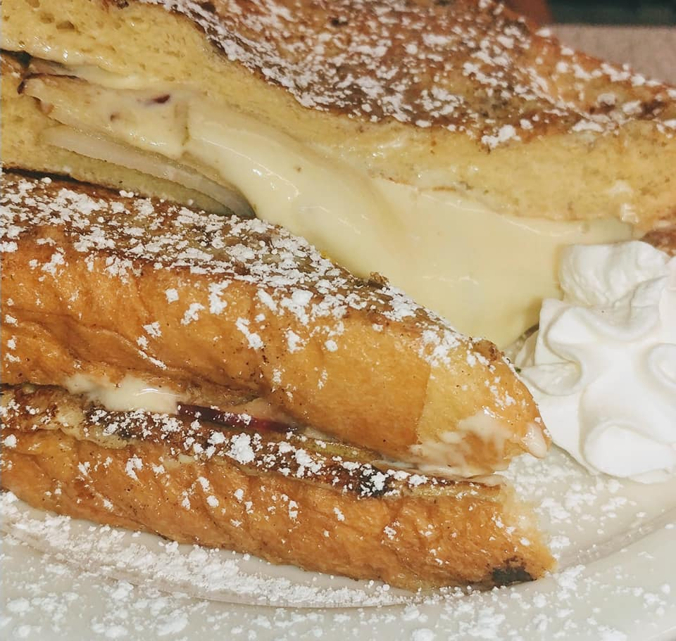 French toast containing apple slices and cream, topped with powdered sugar