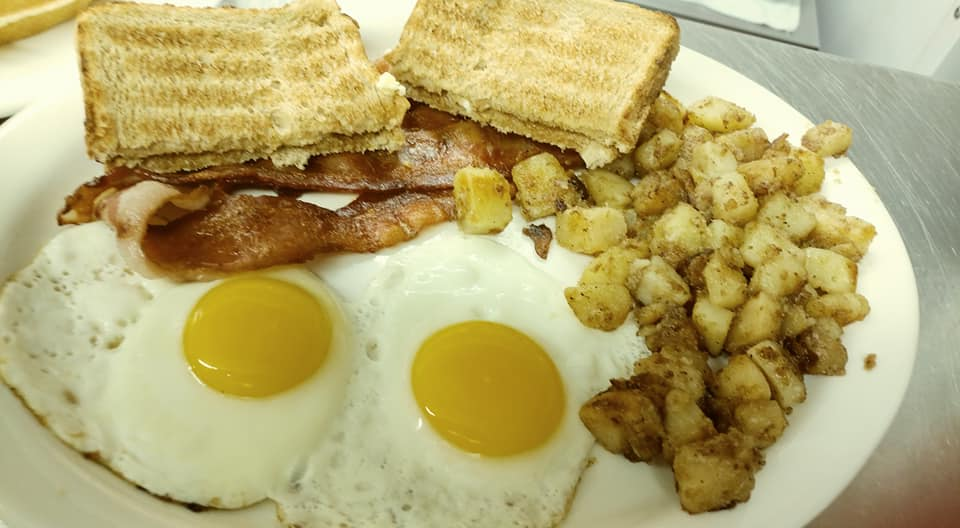 Two sunny side up eggs with bacon, toast and hush puppies