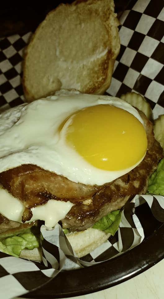 Open faced burger with lettuce, bacon and a suny side up egg