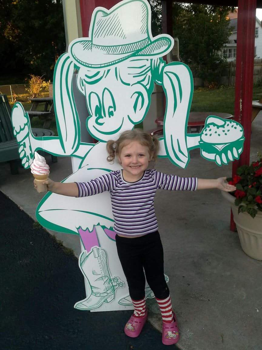A little girl smiling, holding an ice cream cone, posing for a photo in front of Chrissy's logo