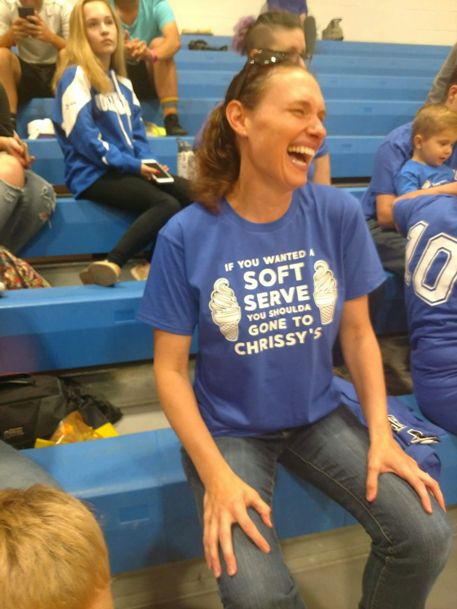 A mother laughing, sitting on stands, wearing a Chrissy's t-shirt