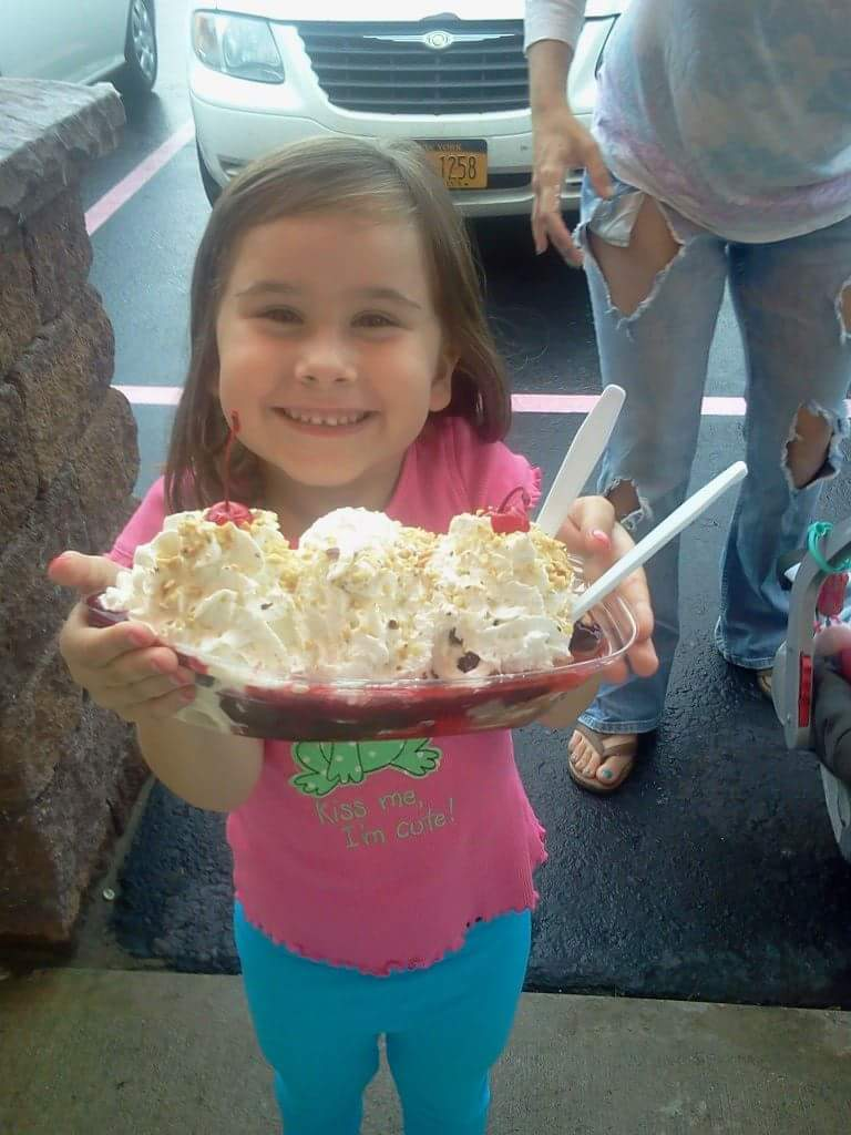 A little girl smiling, holding a bowl of ice cream