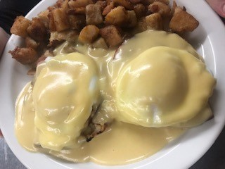 Two eggs benedict topped with hollandaise sauce served with hush puppies