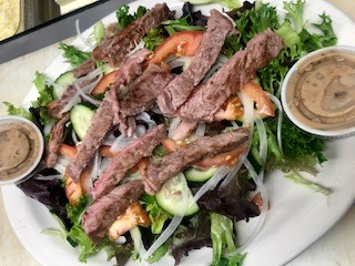 Mixed greens salad served with meat, and dressing