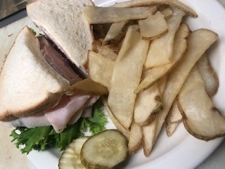 A turkey & pastrami sandwich served with pickles and french fries