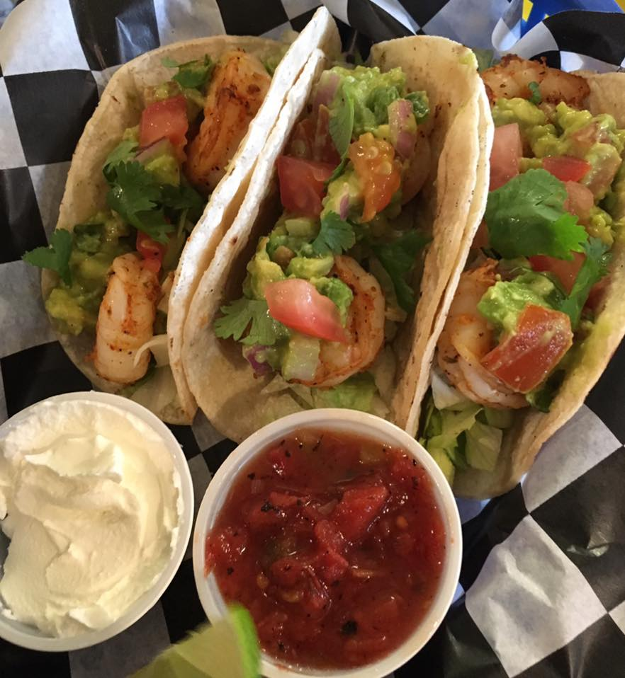 three shrimp tacos with lettuce and dipping sauces