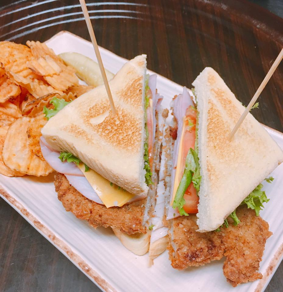 turkey club sandwich with fried chicken and a side of chips