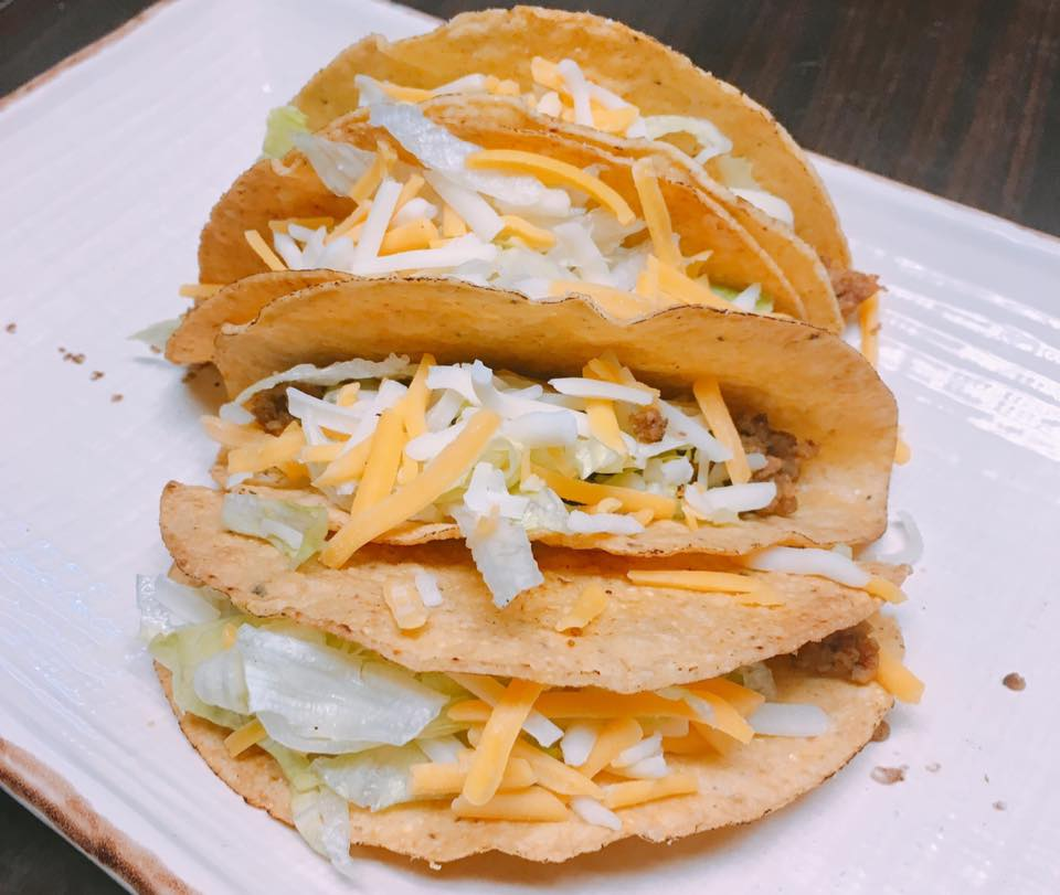 four hard shell tacos with cheese and lettuce