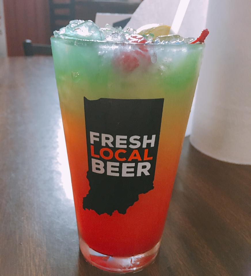 "mixed drink in a glass that says ""fresh local beer"""