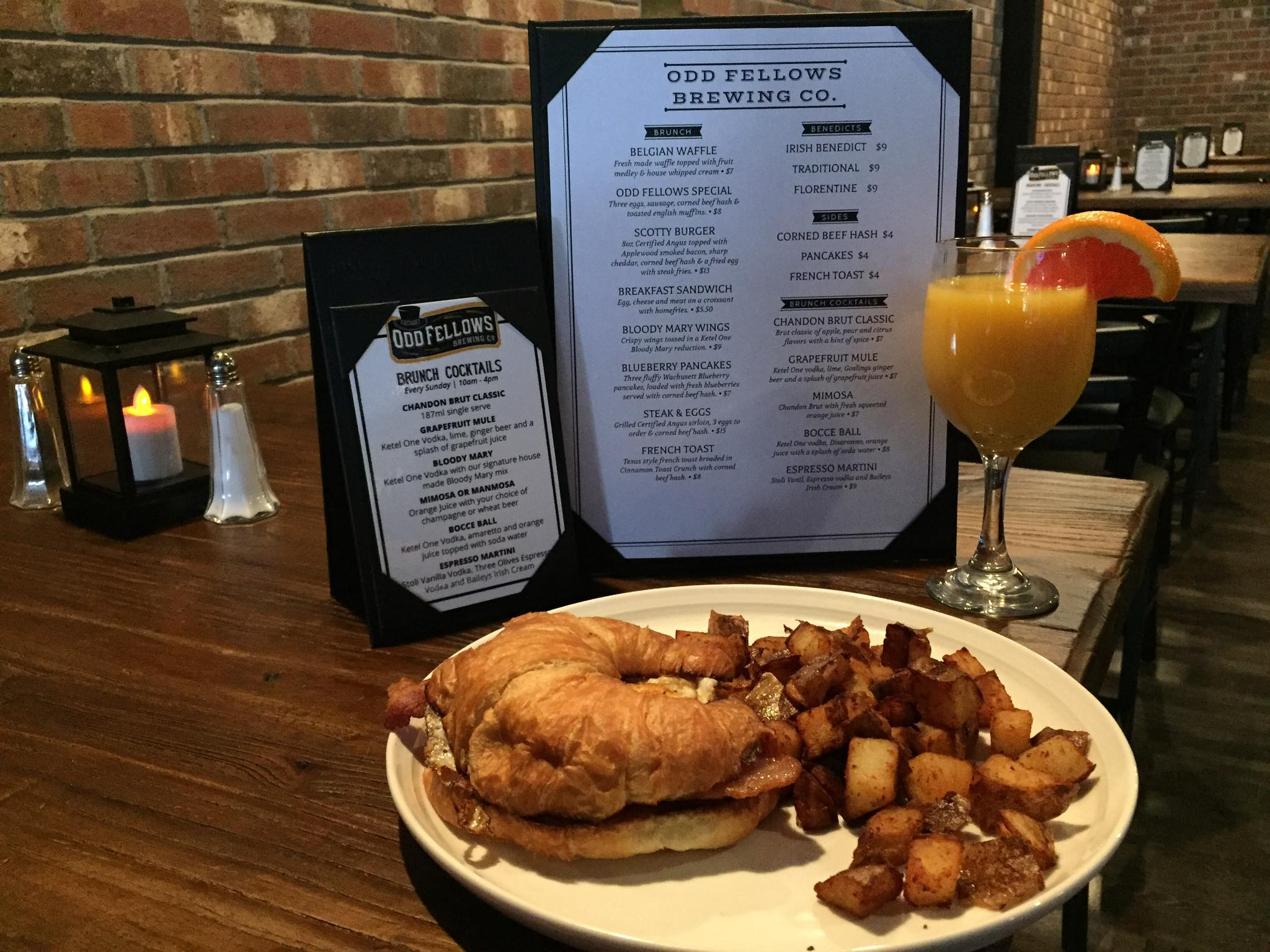 Egg, cheese and (bacon, smoked ham or corned beef hash) on a croissant with home fries, and a glass of orange juice in front of the manual menu