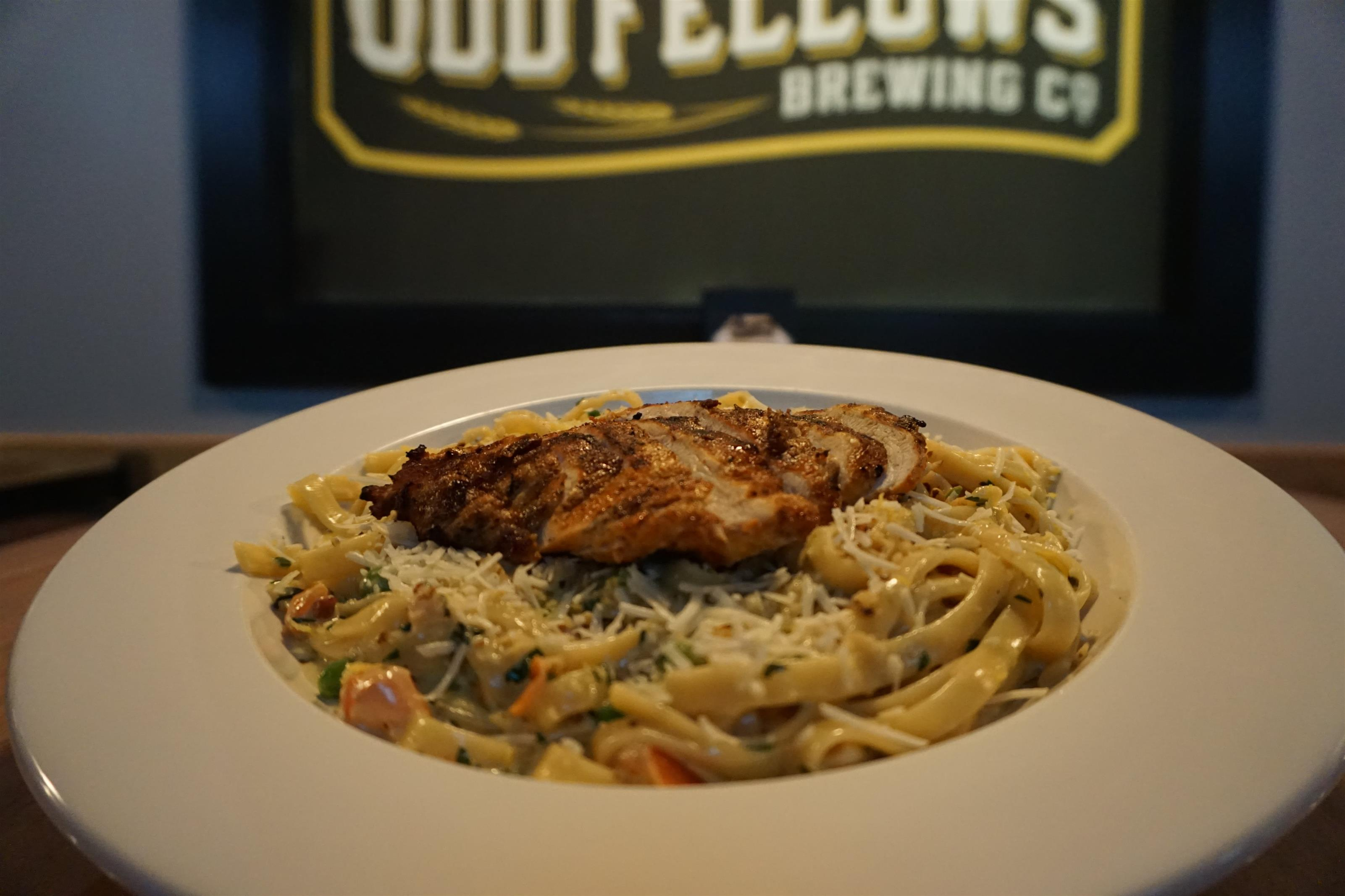 Linguine topped with grilled chicken and parmesan cheese
