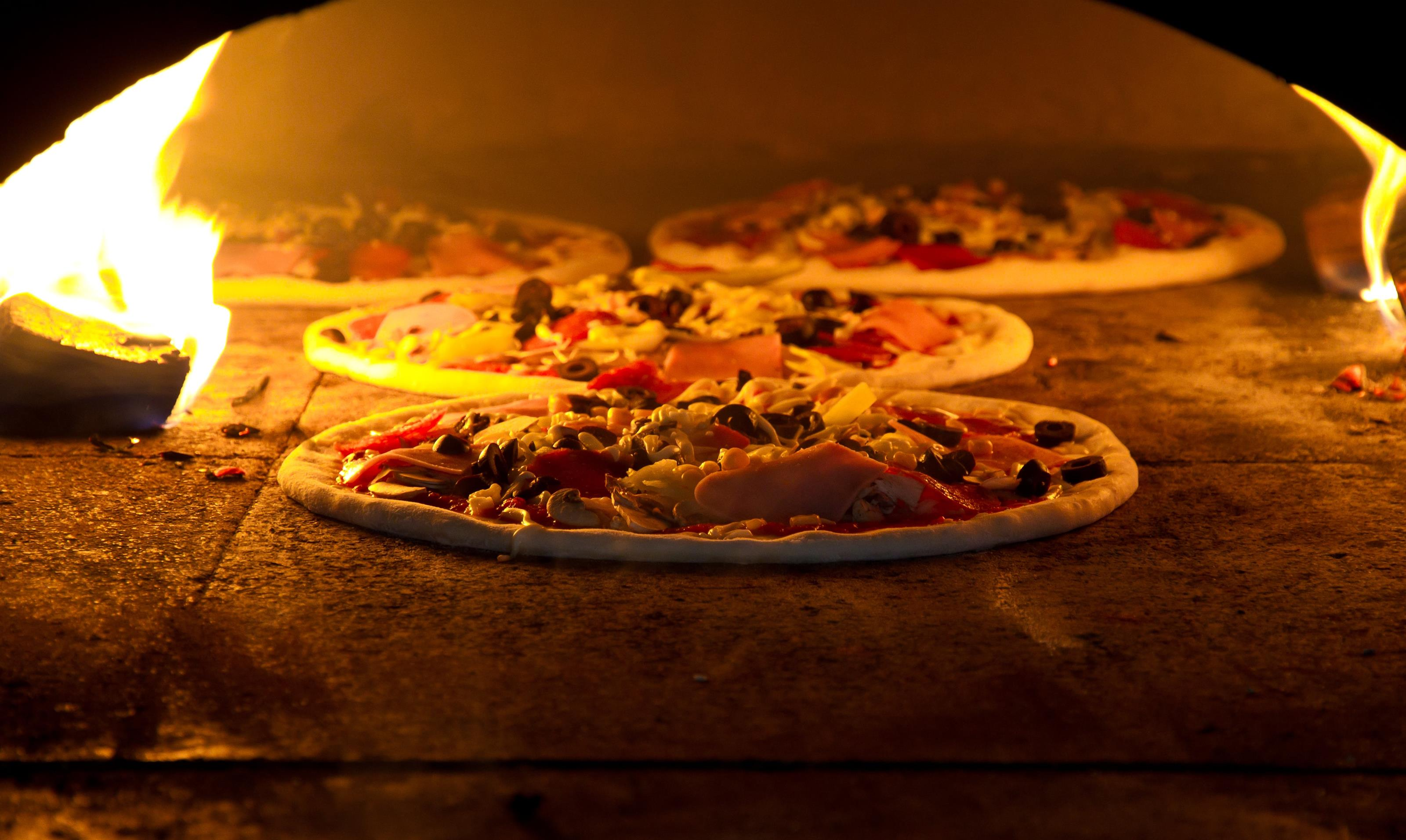 several pizzas in brick oven