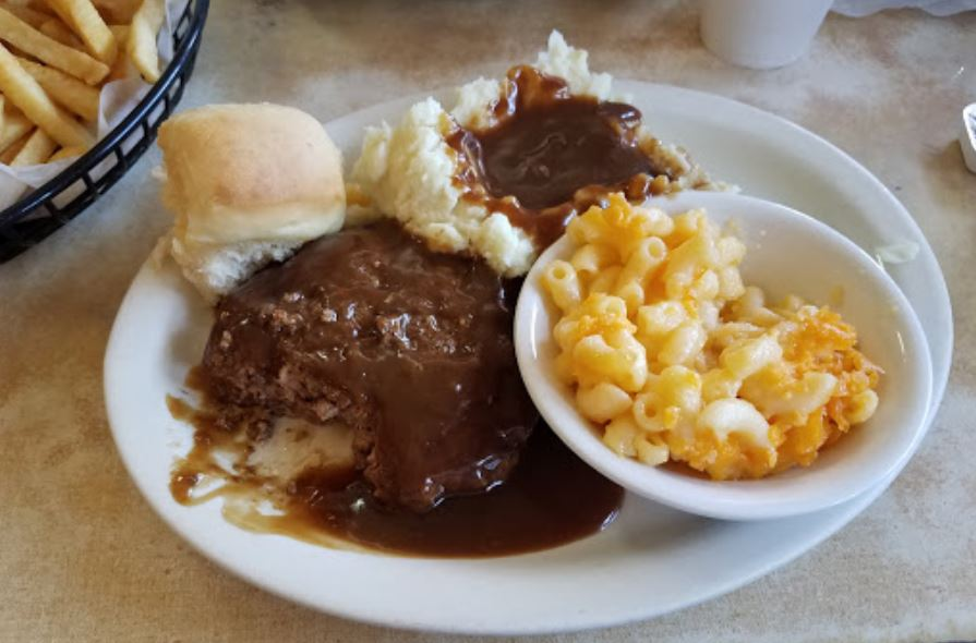 Hamburger steak smothered in gravy, side of mac and cheese, mashed potatoes and gravy, biscuit.