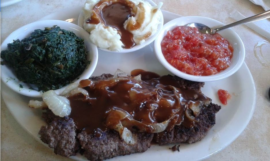 Beef liver smothered in gravy and onions with side of spinach and mashed potatoes & gravy.