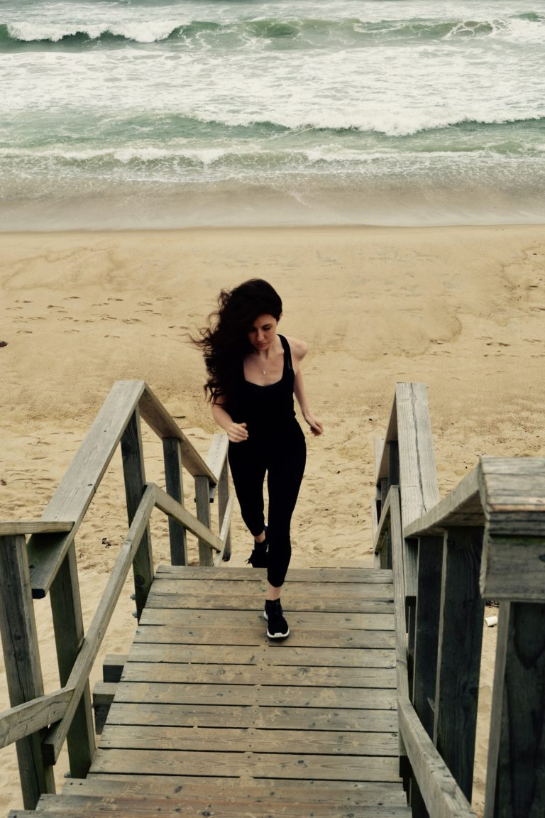 Doctor Alex jogging on stairs leading away from a beach