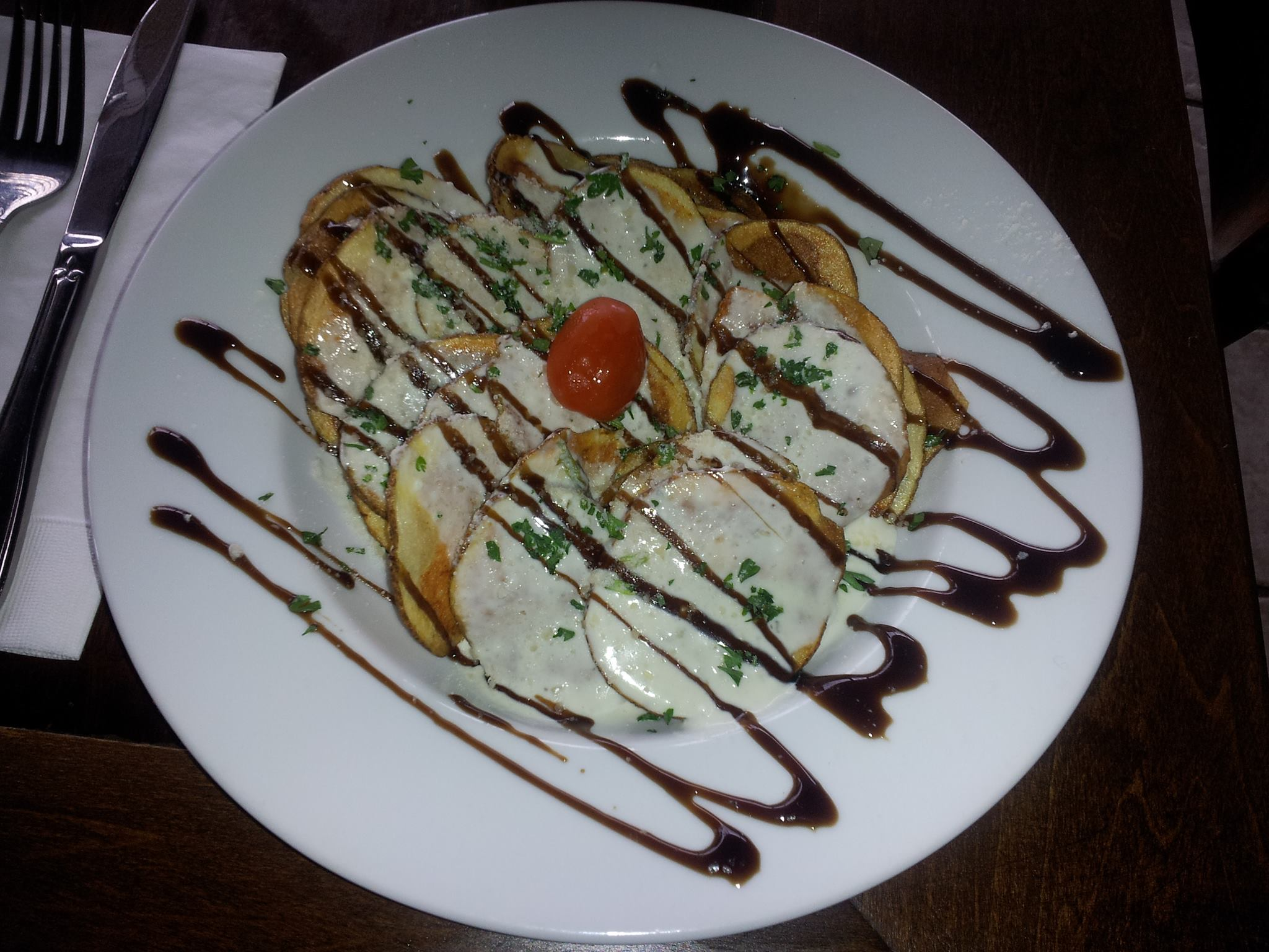 Potato slices with dressing and balsamic glaze.