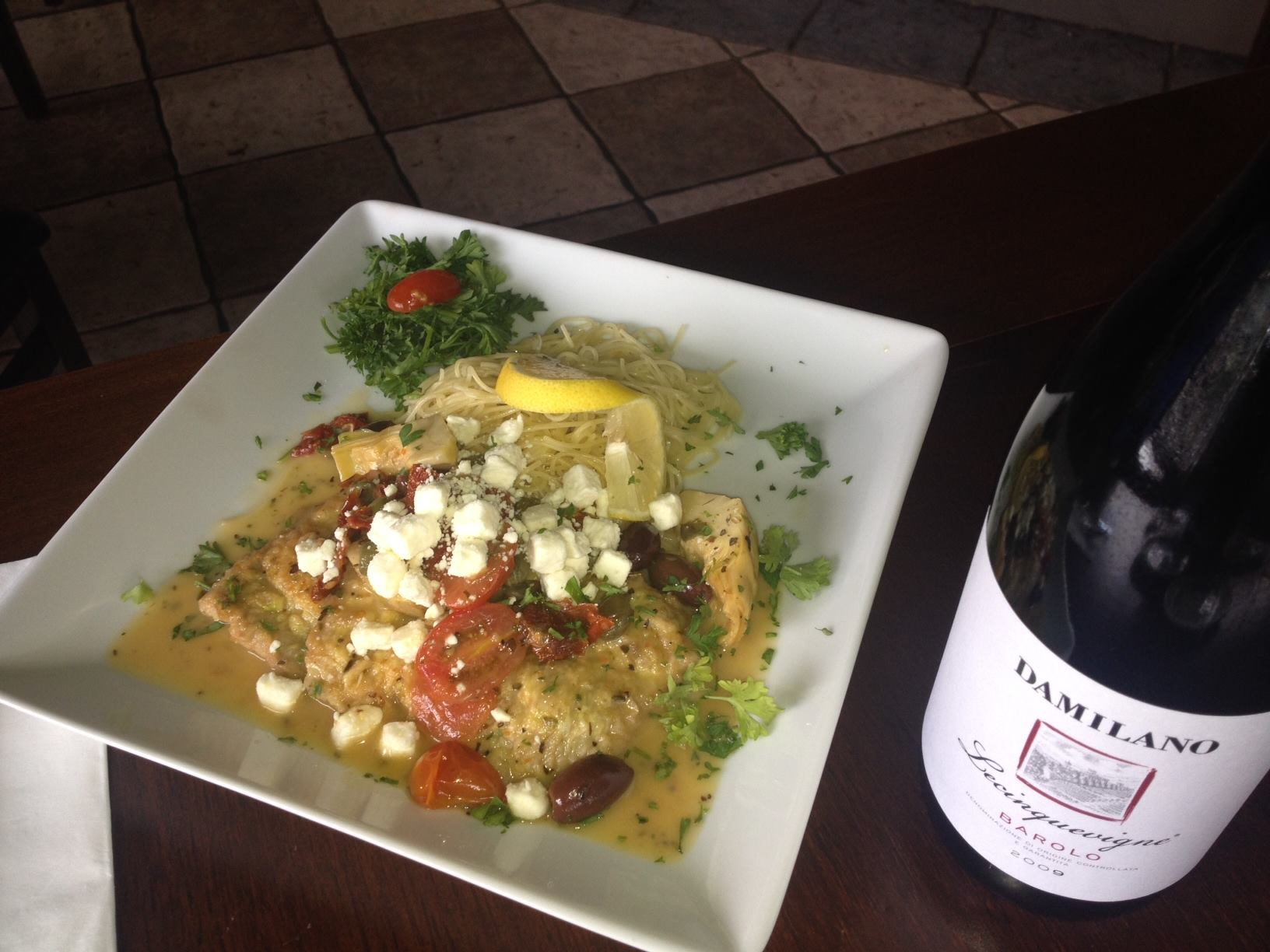 Chicken piccata with angel hair on dish next to wine bottle.
