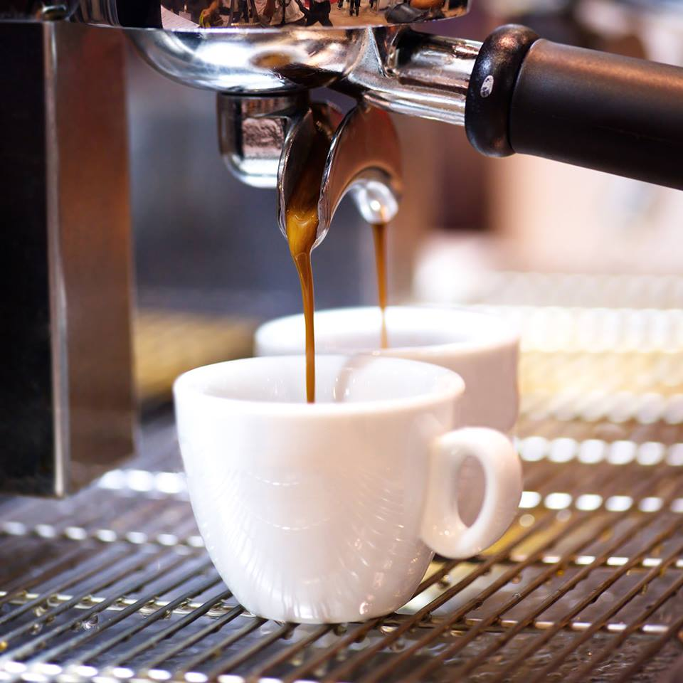 Cup of espresso filling under machine