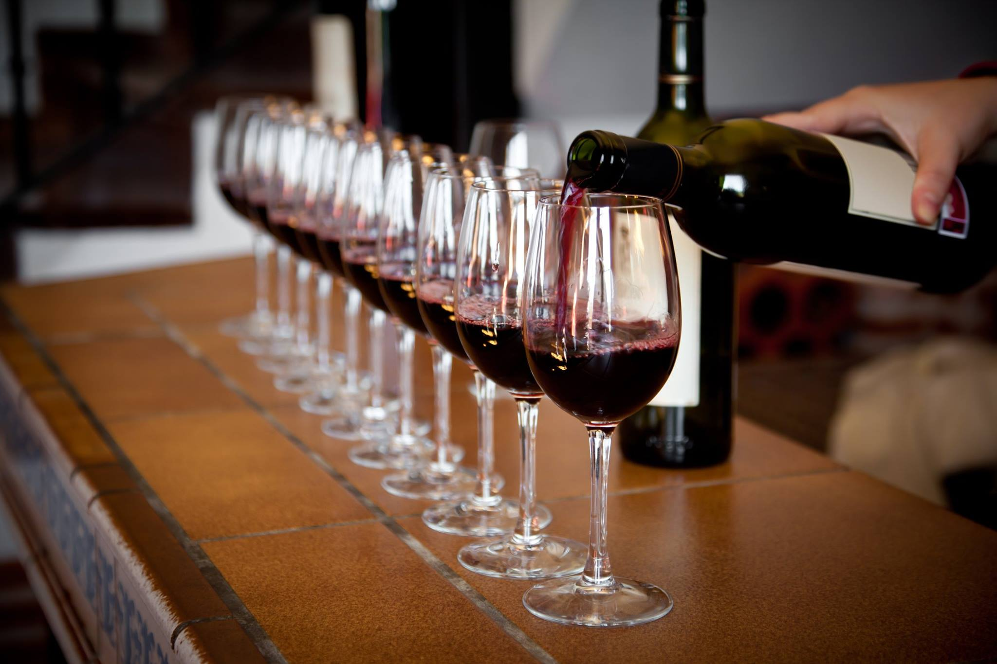 glasses filled with red wine lined up on counter