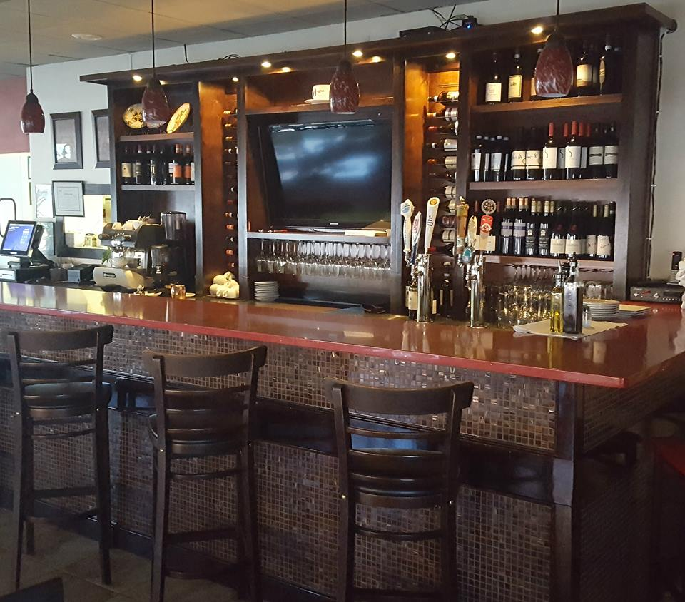 Bar area with high top chairs, liquor shelves, beer taps, TV set in wall