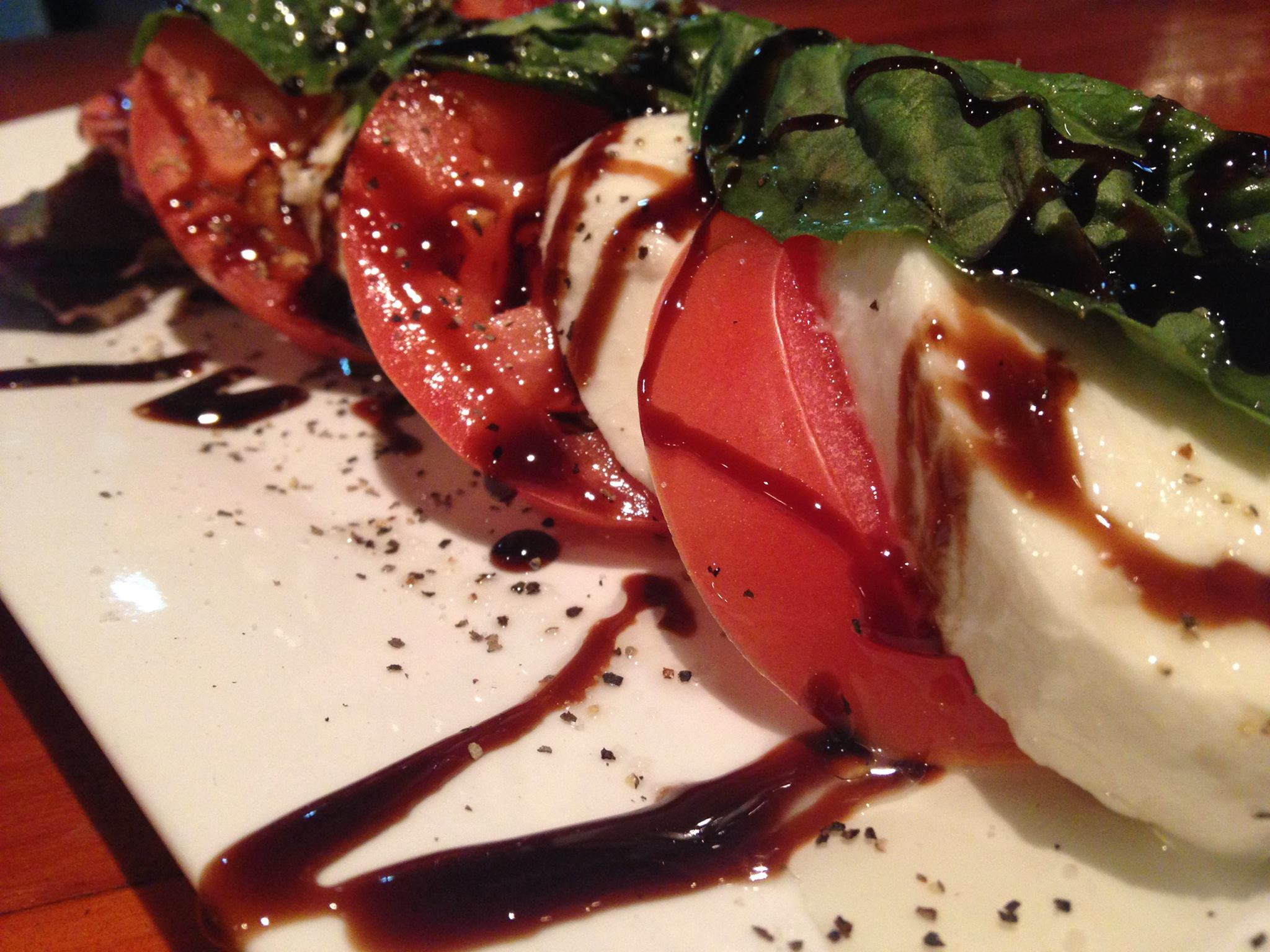 Tomatoes, basil, fresh mozzarella on dish with balsamic drizzle.