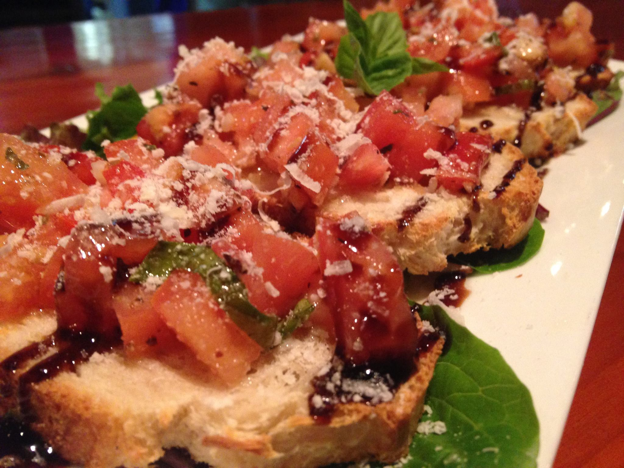 Bruschetta with tomatoes, shaved parmesan and balsamic glaze.