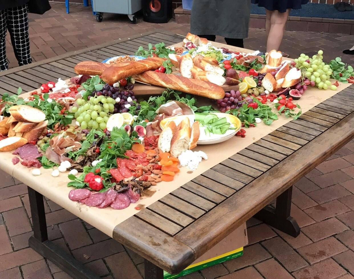 assortment of bread, italian cured meats, grapes, peppers, cheeses on large wood table.