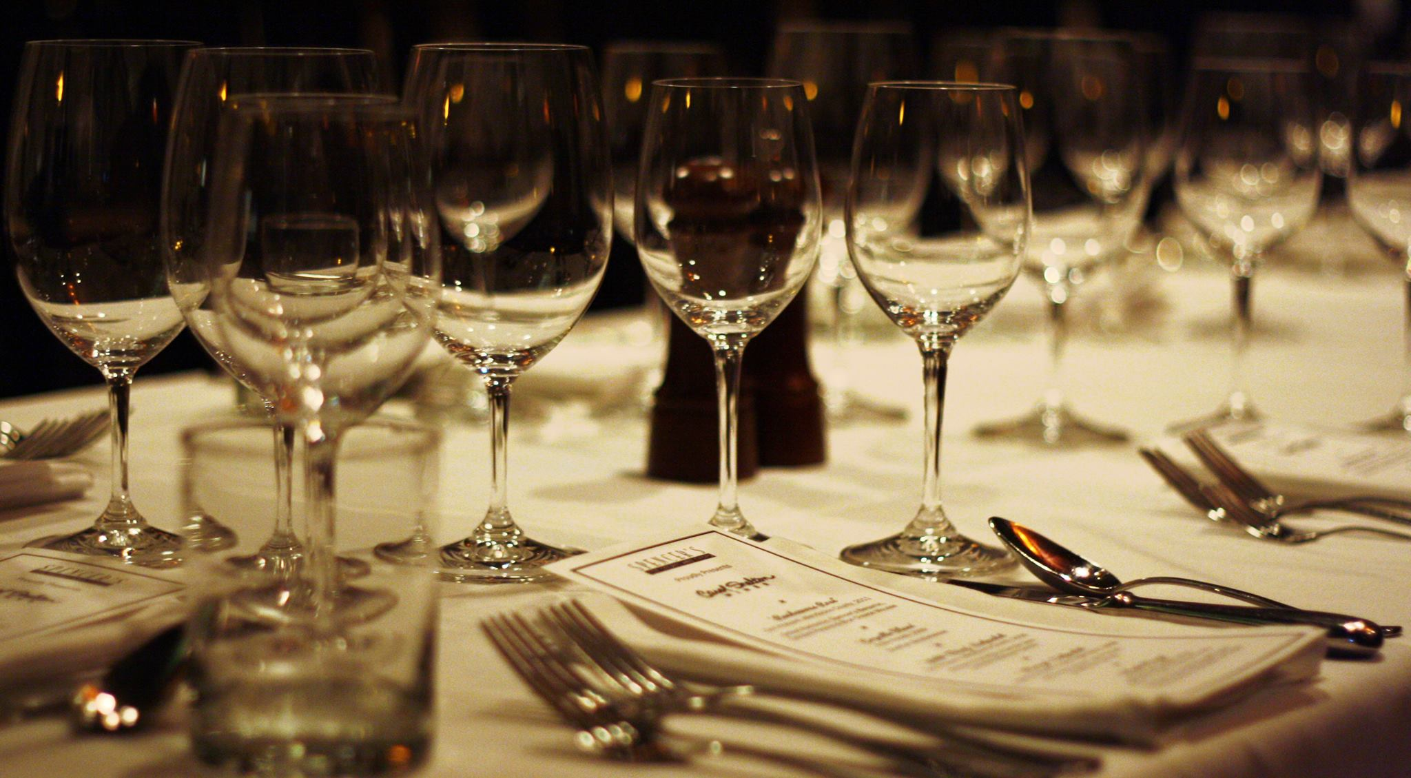 Water glasses and silverware on white table cloth