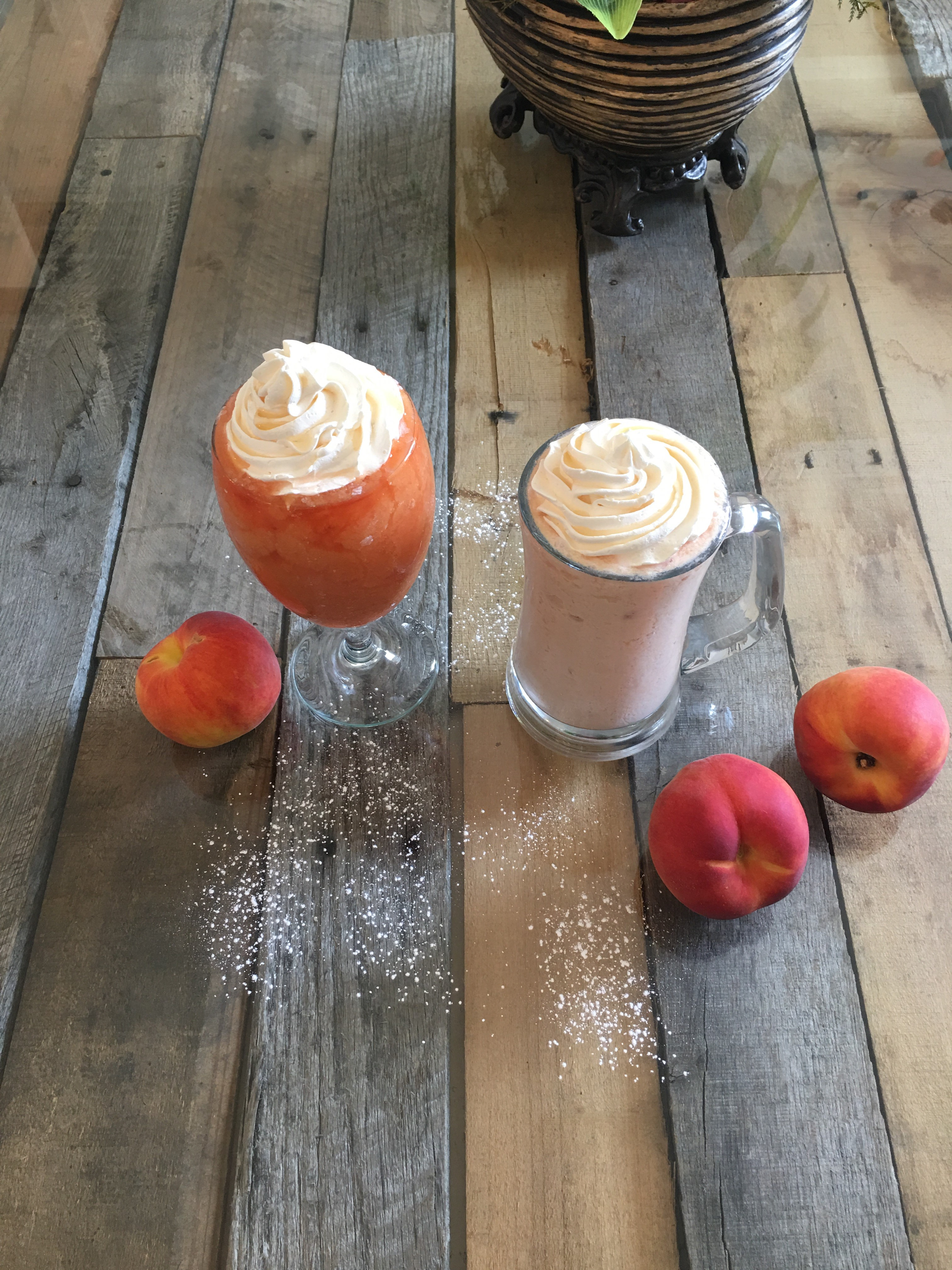 Image of two Orange and Peach smoothies, topped with a whip cream.