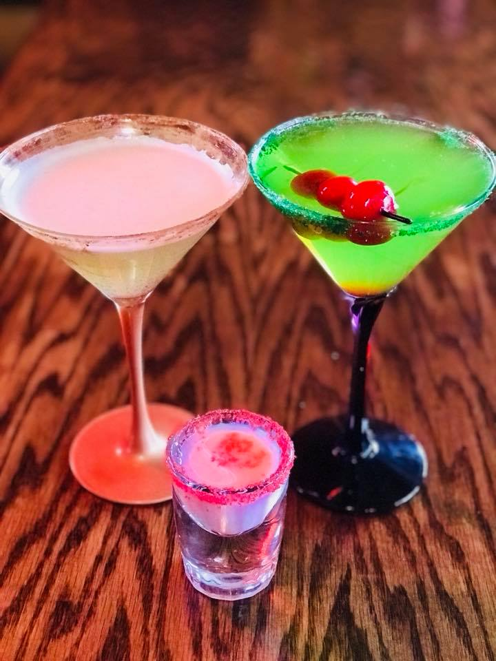 Green Martini with 3 cherries for garnish next to a pink mintini with sugar around the rim and a pink shot with pink sugar around the rim