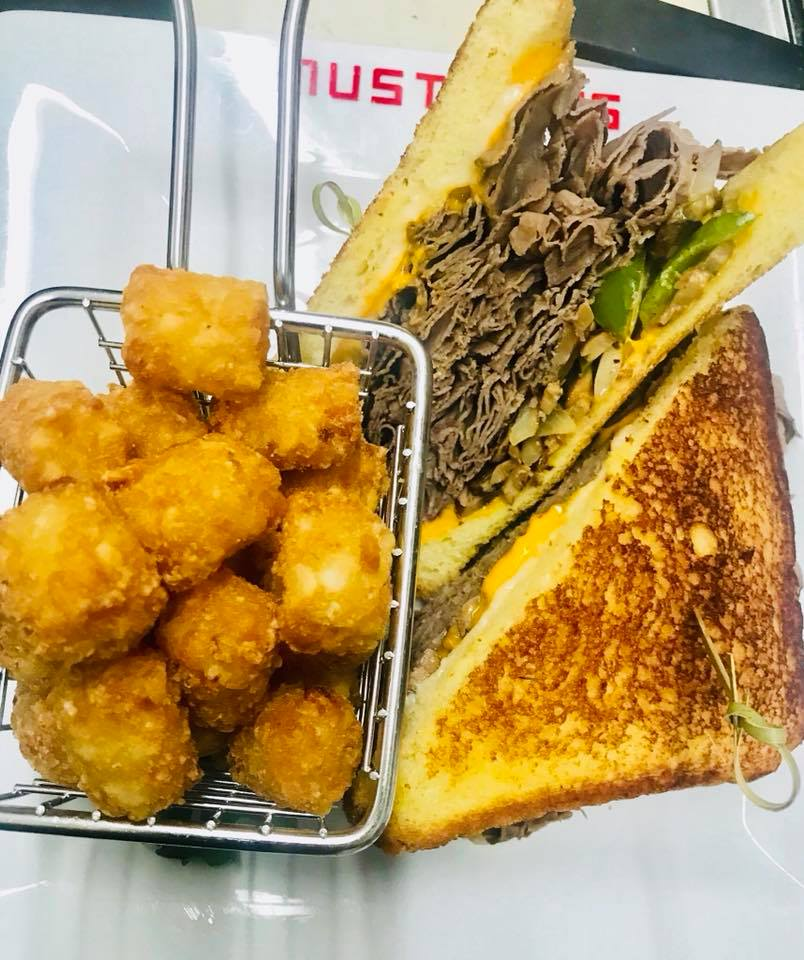 Italian beef piled up with sautéed green peppers and onions with melted Swiss and American cheeses served on grilled Texas toast with a side of tater tots