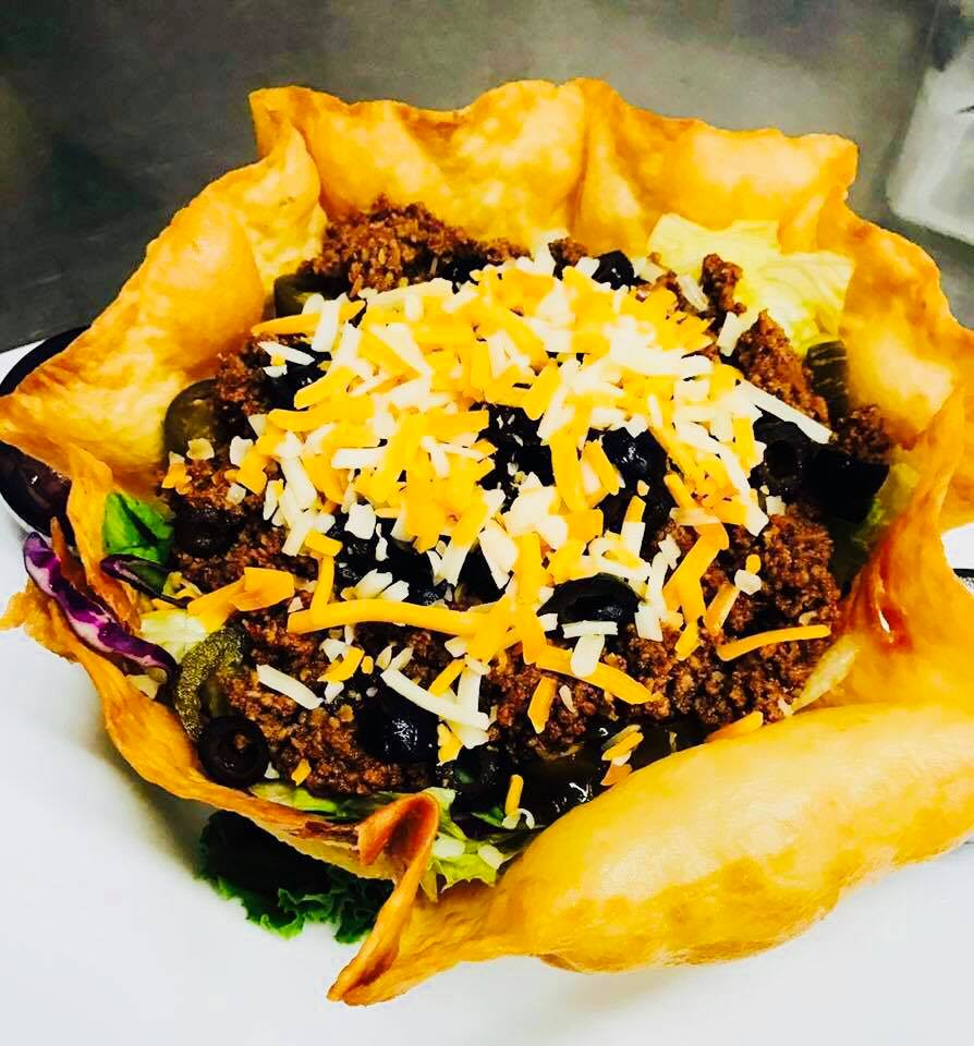 Taco bowl with shredded mexican cheese on top inside a fried tortilla bowl