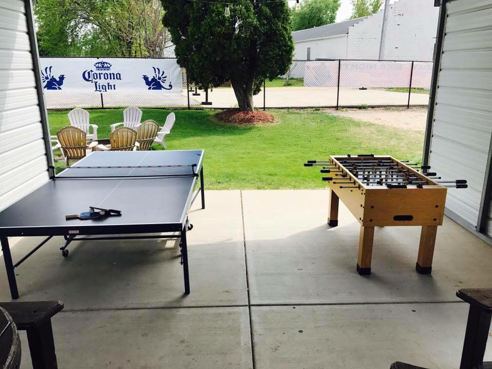 Outside area with foosball and ping pong table with fire pit in the background