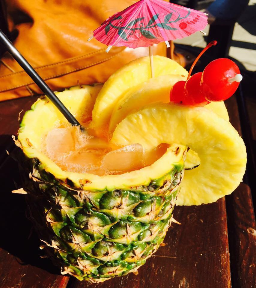 Tropical cocktail inside a real pineapple with slices of pineapple hanging out the side