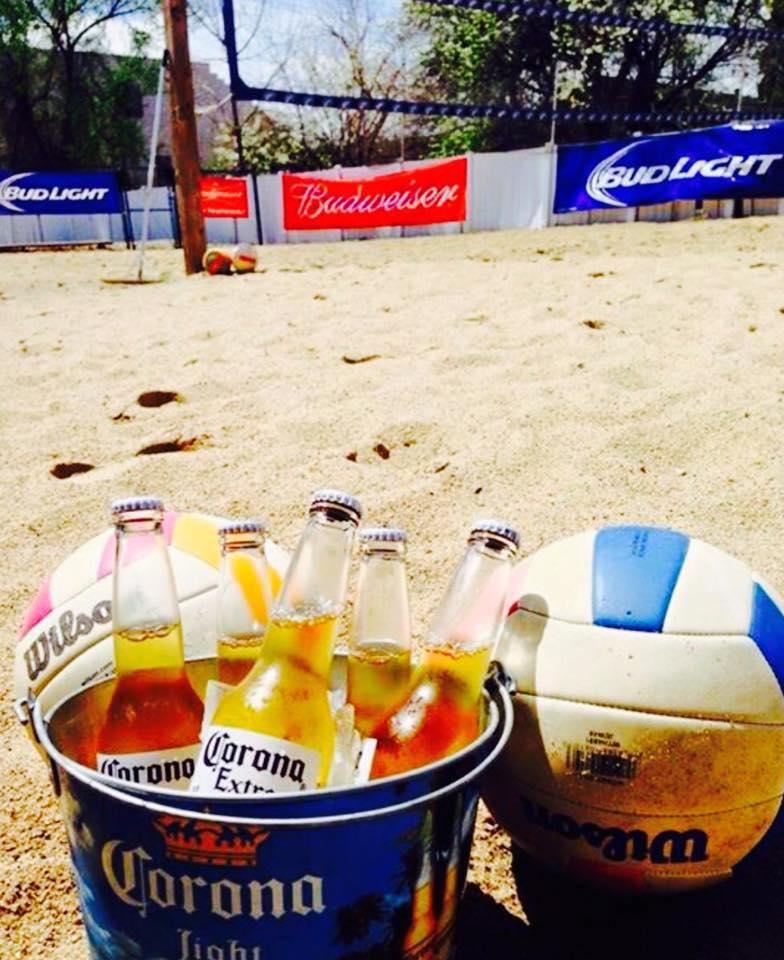 Beach volleyball set up with a bucket of corona extras in front of a pink volleyball and a blue volleyball in the sand