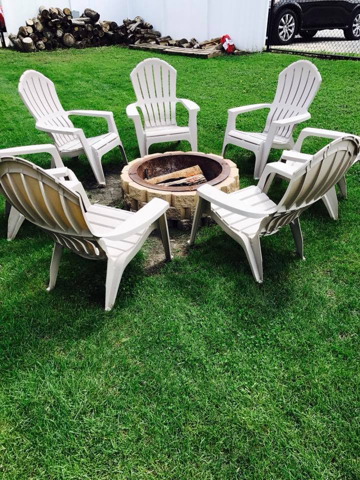 Outside seating area with white lawn chairs set around a fire pit