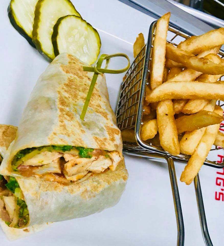 Chicken burrito with yellow peppers and lettuce with a side of fries