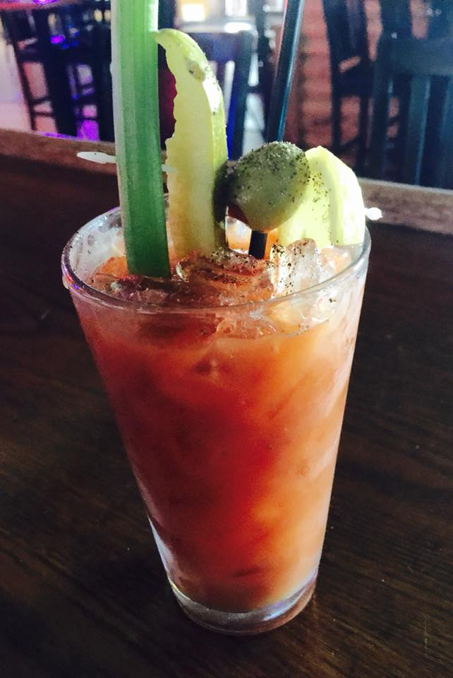 Bloody Mary with celery stick, pickle, olive and lemon sticking out