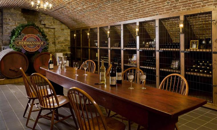 The Hermannhof Library Cellar has a tile floor, a wooden rectangular table in the middle with 8 chairs around it.  In the background is the Hermannhof Wine Library with 10 cabinets with different wines of different ages.