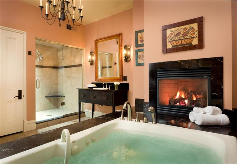 Full bathtub in front of a fire place, shower in the background